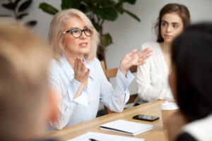 Older woman imparting wisdom to younger co-worker